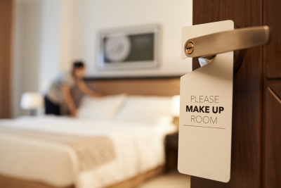 maid cleaning the room with please make up my room sign on the door