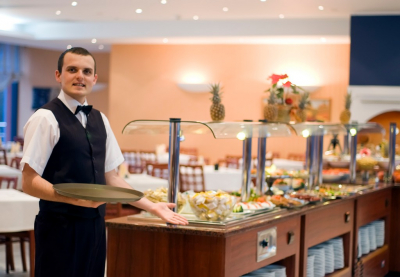 handsome young waiter presents an impressive buffet in a hotel